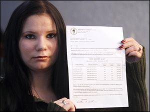"""Danielle """"Embyr"""" Lindner holds a letter she received that is supposedly an """"audit"""" of her voting history.."""