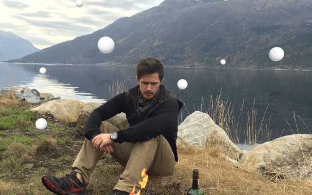 Pierce Brown sits by a camp fire