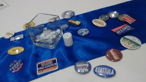 A table setting with political campaign buttons, candle, and vase