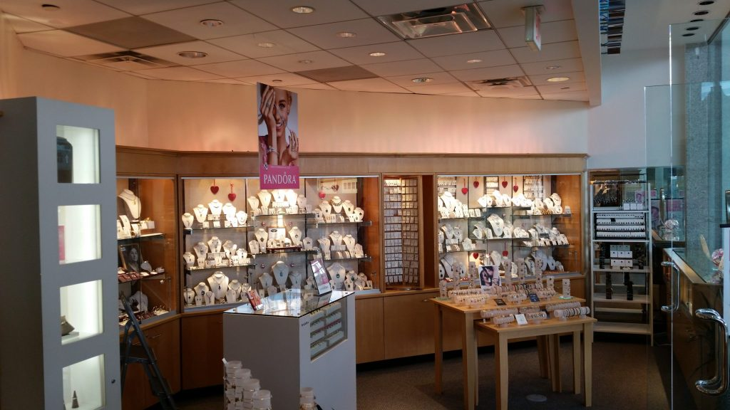 Before photo of the interior flooring, lights, and jewelry display cases.