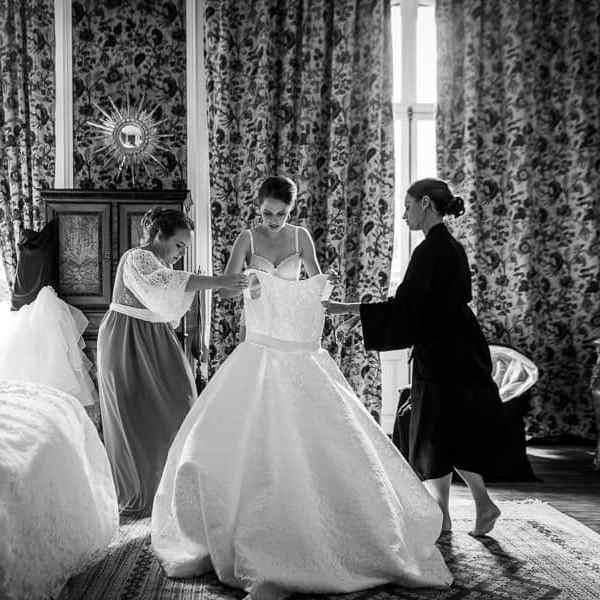 Les préparatifs du mariage l'habillage de la mariée enfile sa robe de mariage