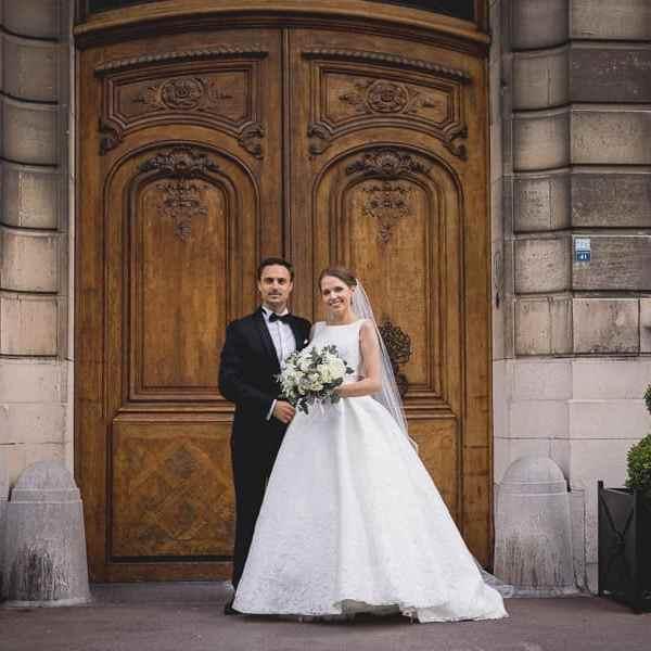 Superbe photo de couple posé des Mariés devant la porte en bois de l'hôtel privé