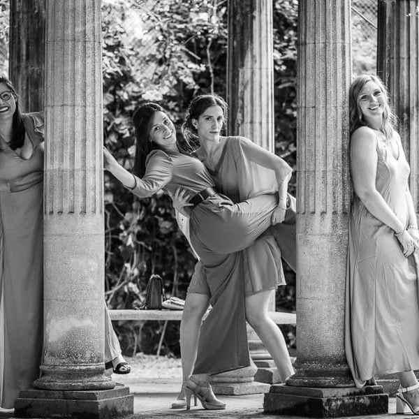 Les filles invités du mariage tape la pose photo derrière les colonnes de marbre