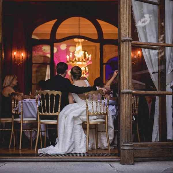 Photo des mariés assis à table prise de dos en soirée de mariage jolie couleur douce