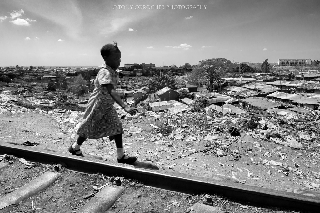 Africa, where are you going ... | A young girl playing on the railway that runs through Kibera (the second largest slum in the world - Nairobi). All you can see in the background is Kibera with over one million people. While I was taking this picture my mind kept thinking about what kind of future awaits the African countries.