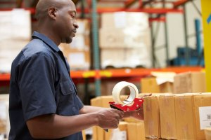 Logistics Worker Sealing Up Package
