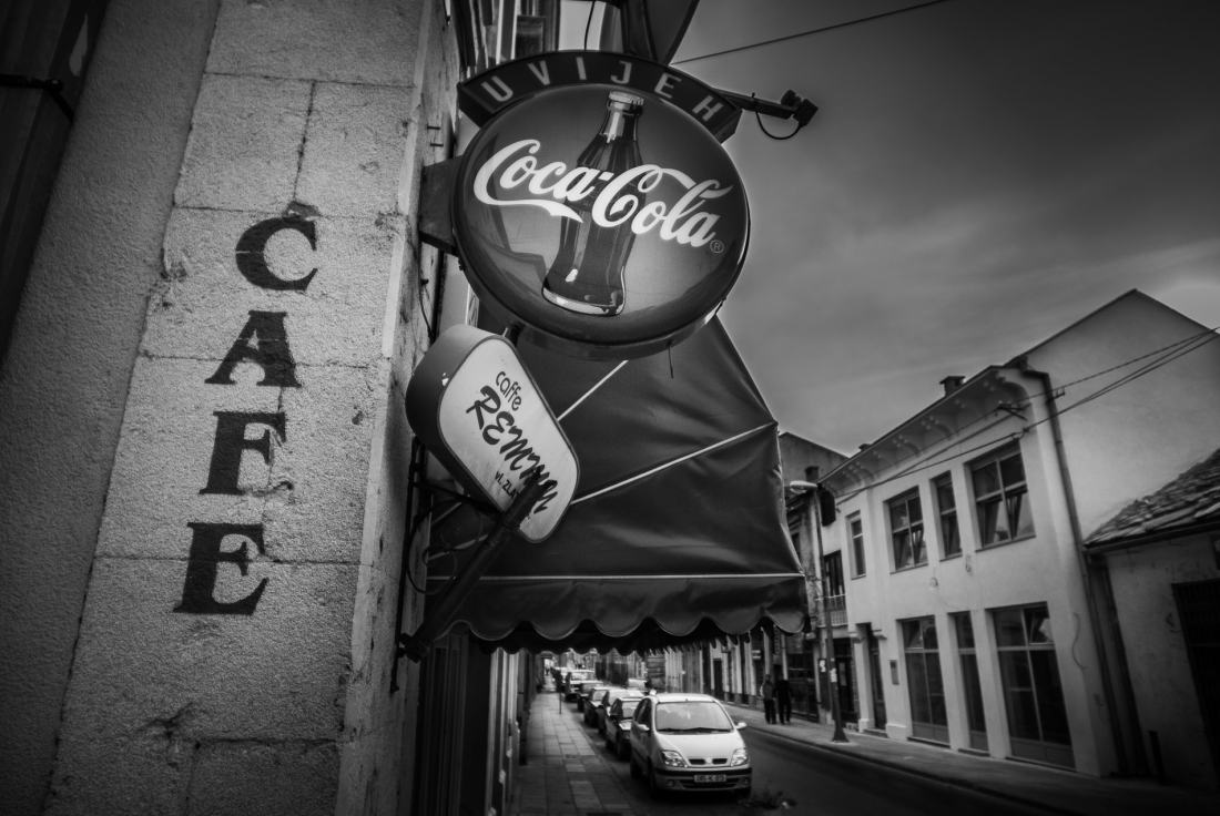 Black and white photograph of a coca cola sign outside a cafe in Mostar, Bosnia and Herzegovina