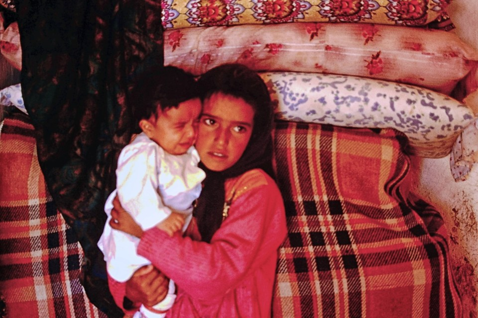 Mother holding baby in front of red blanket