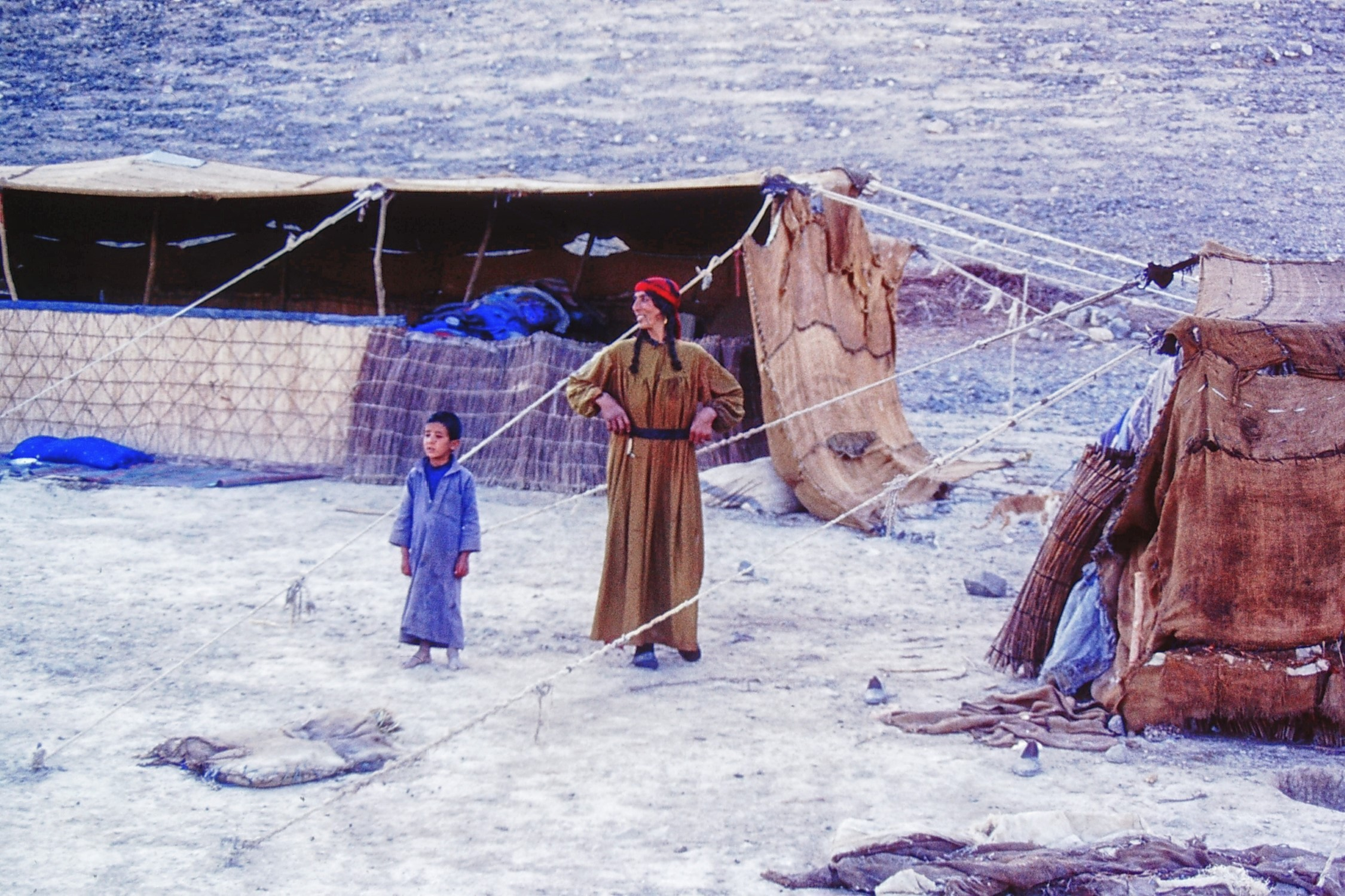 Woman and boy in front of makeshift tents
