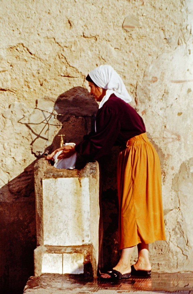 Woman washing clothes under a street fountain