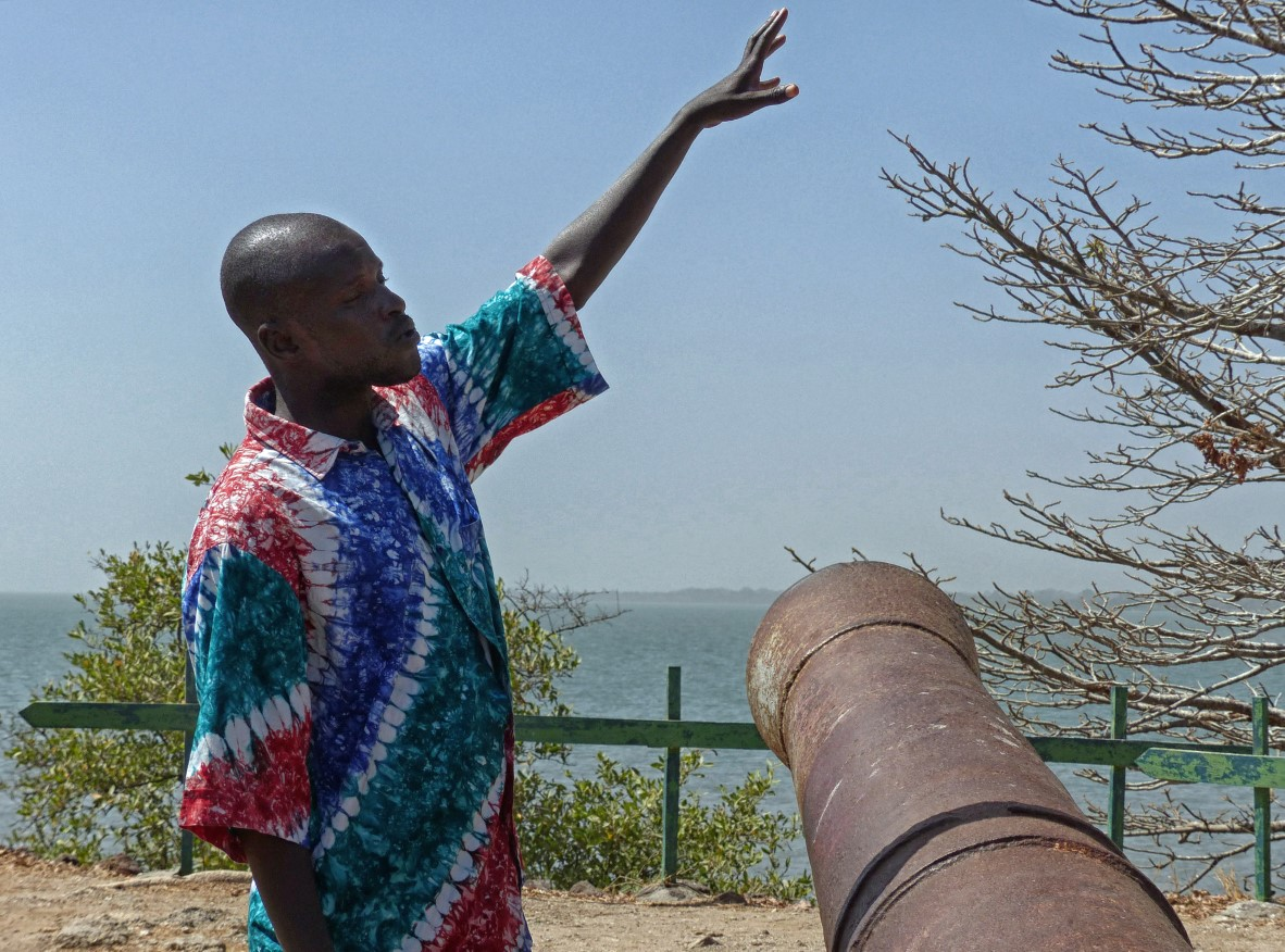 Man pointing by large rusty cannon