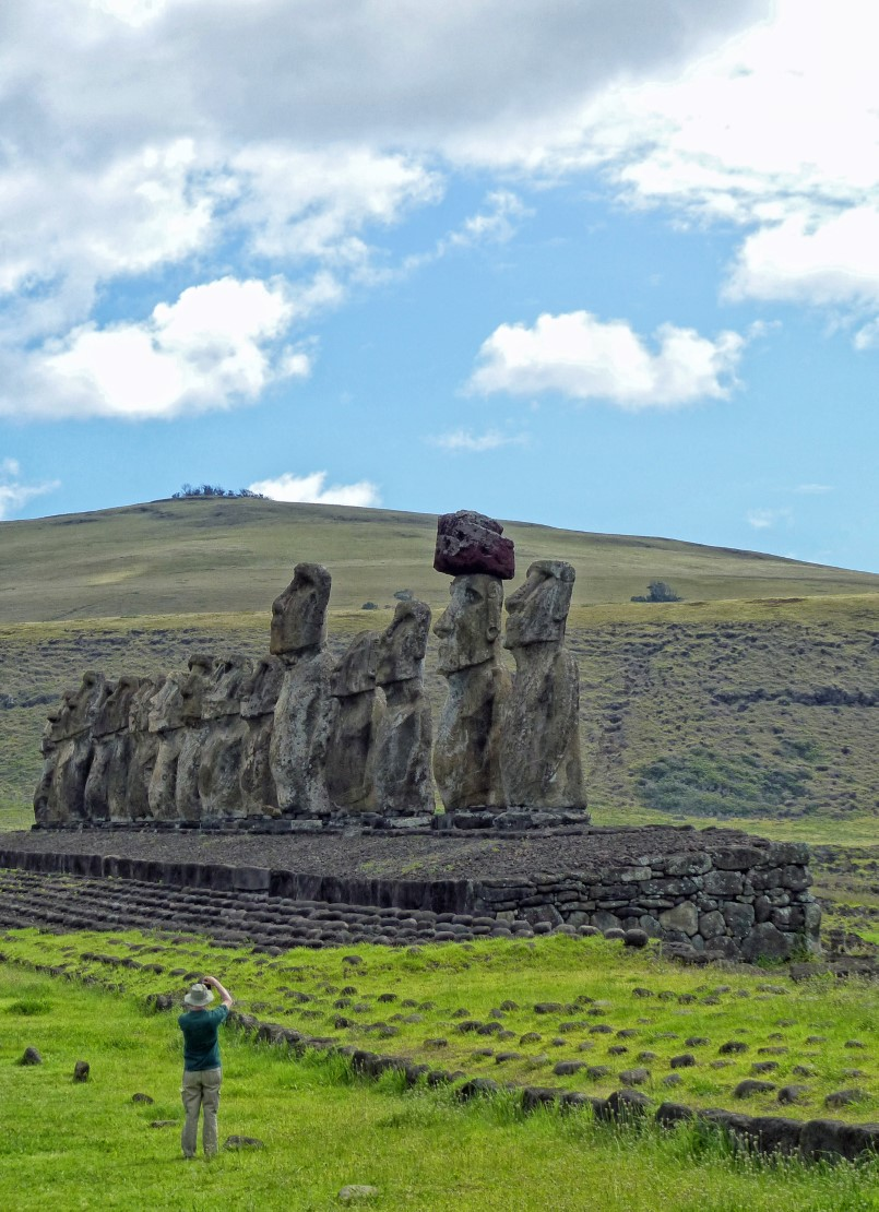 Row of moai with person photographing them
