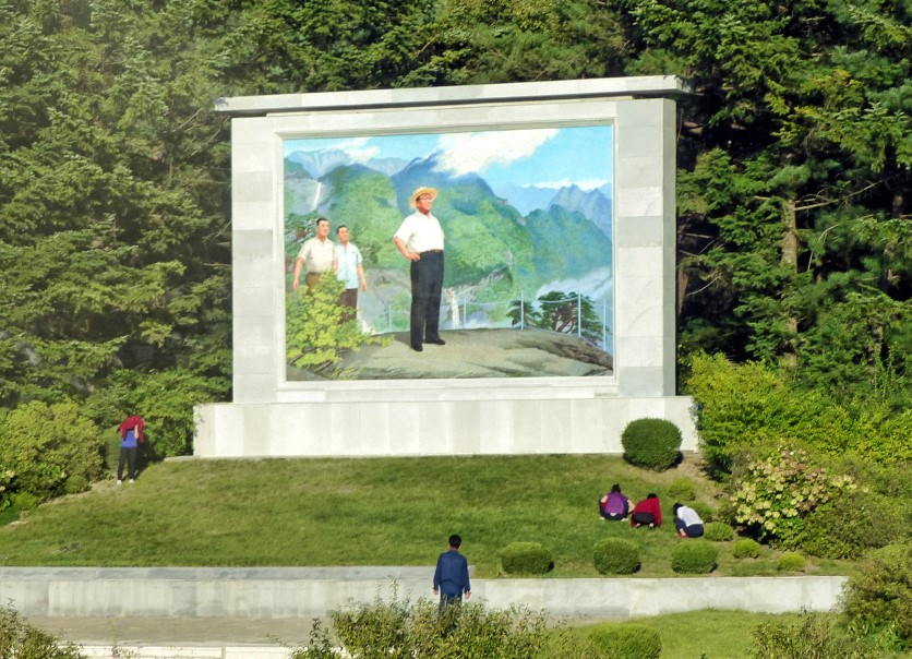 People gardening on hill with large mosaic of Kim Il Sung