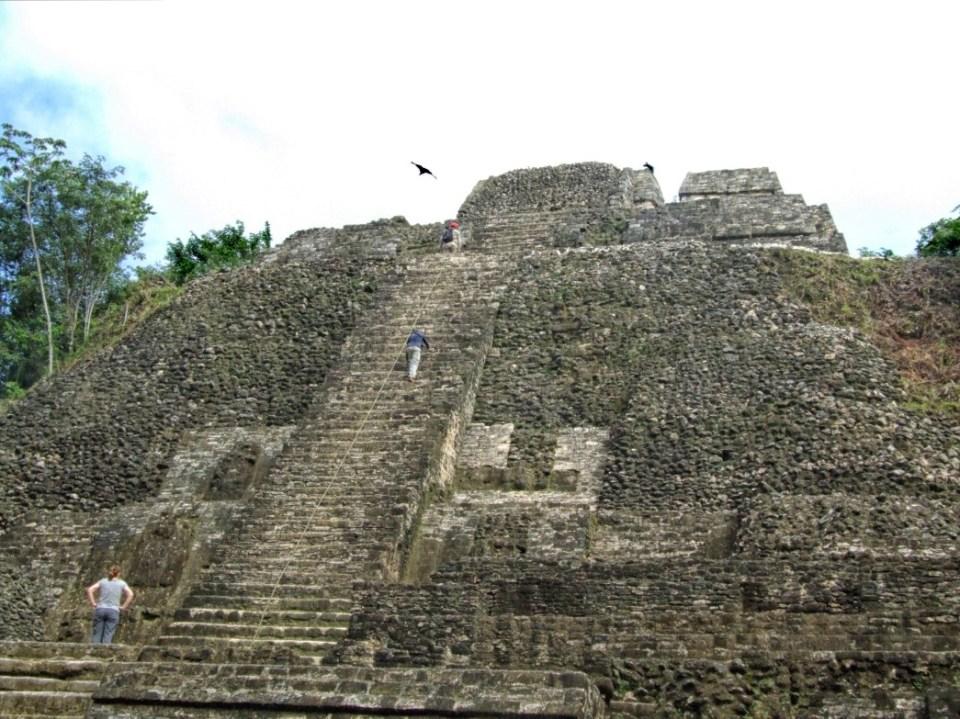 People climbing up a tall Mayan temple