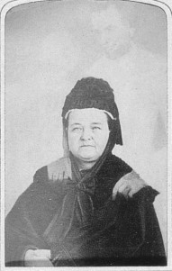 Old photo of a woman with ghostly figure behind
