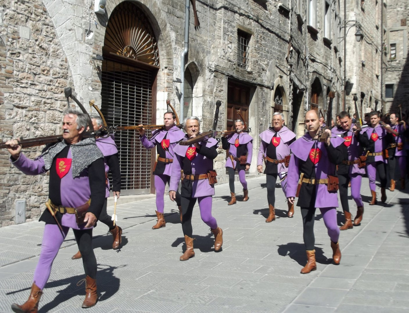 Men in purple and black carrying crossbows