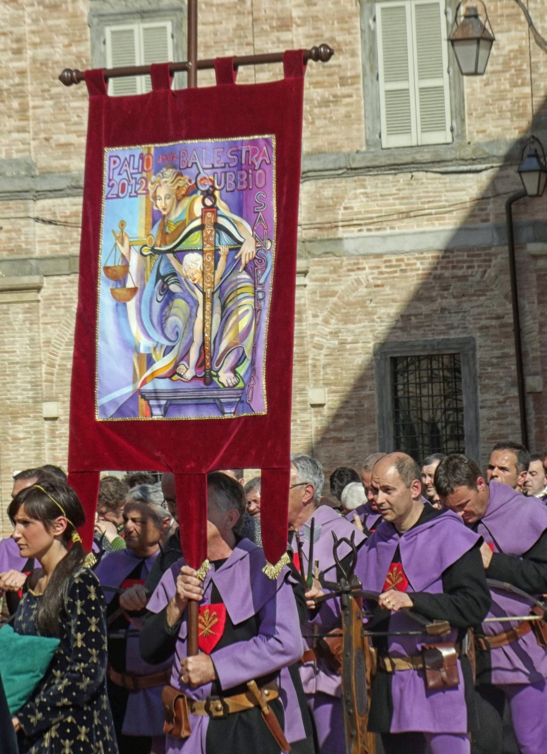 Men in purple and black with large banner