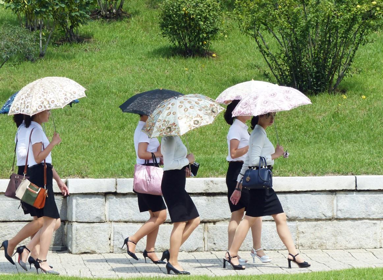 Six young women walking with parasols