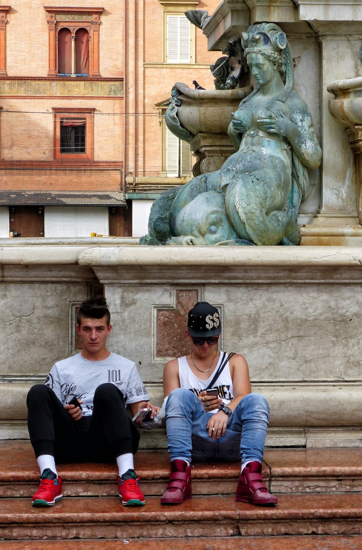 Two young men sitting on the steps of a fountain