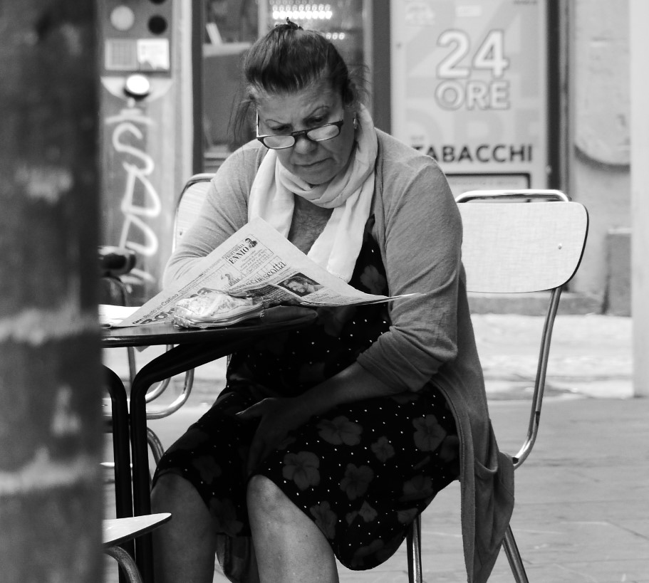 Woman reading a newspaper in a cafe