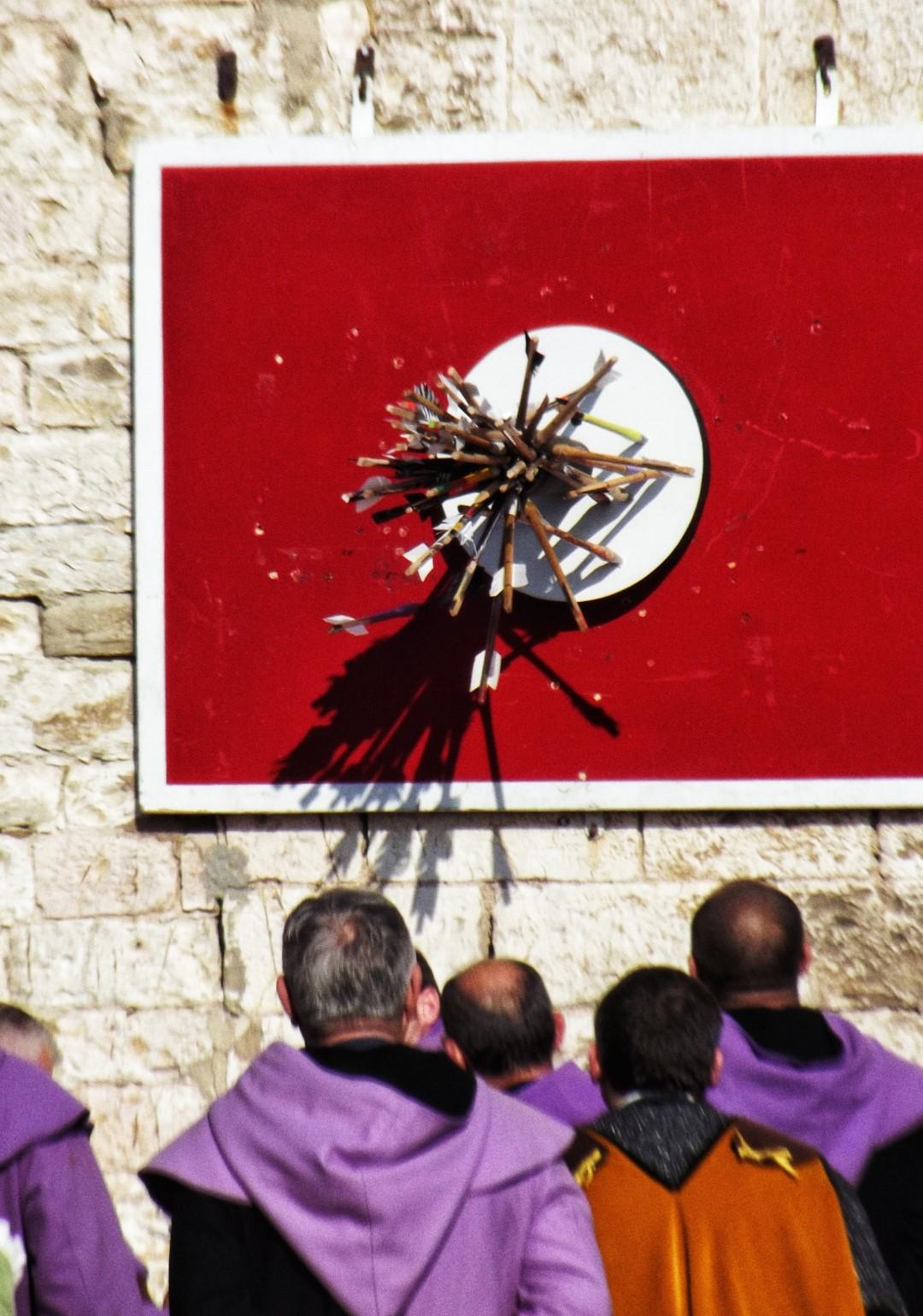 Men crowding around target full of arrows