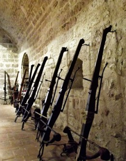 Crossbows propped against a stone wall