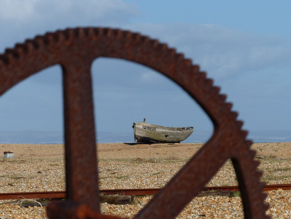 Old boat and rusting wheel on a shingle beach