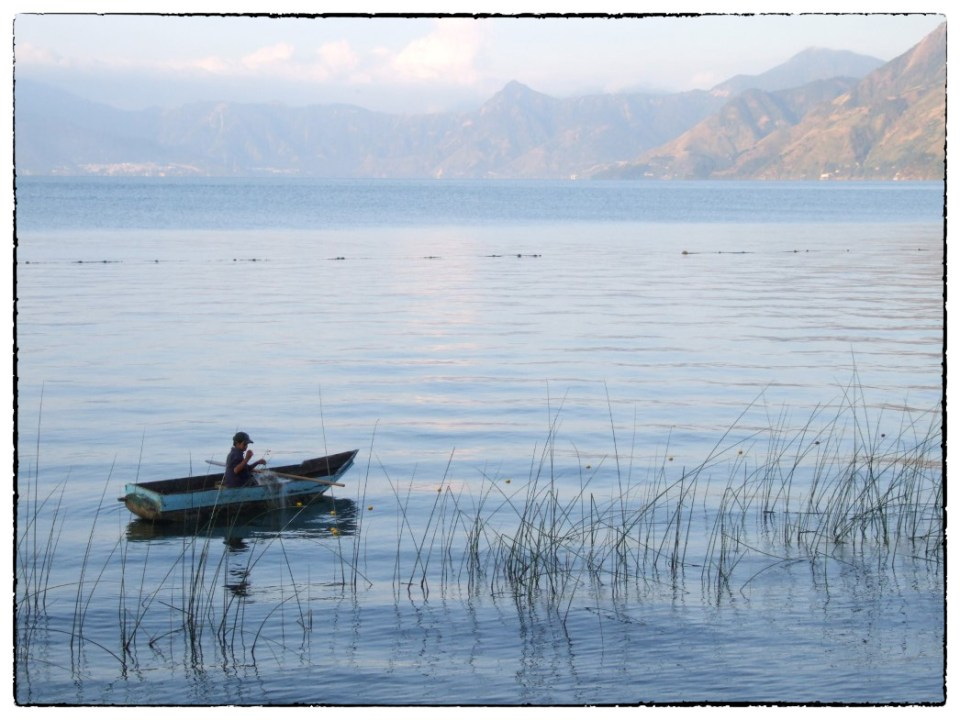 Small fishing boat with a man in it, on a large lake