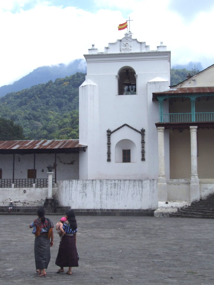 Two women walking across square with white church