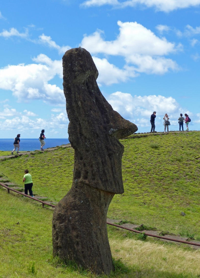 Large stone head and tourists passing