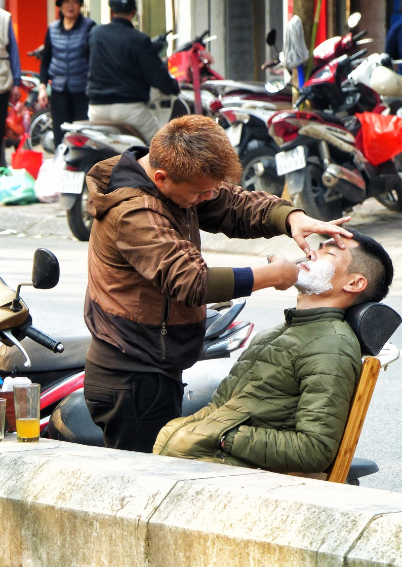 Man being given a shave on the street