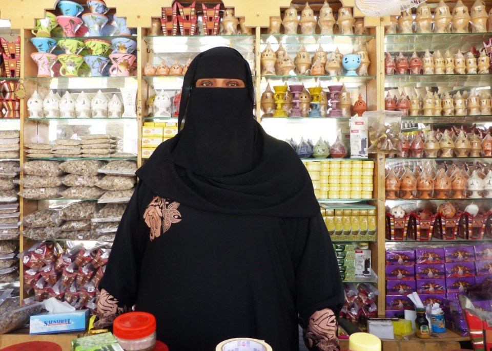 Woman in black niqab at a market stall