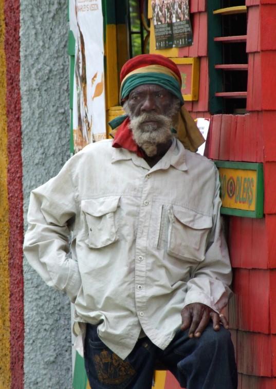 Elderly rasta leaning on wooden booth