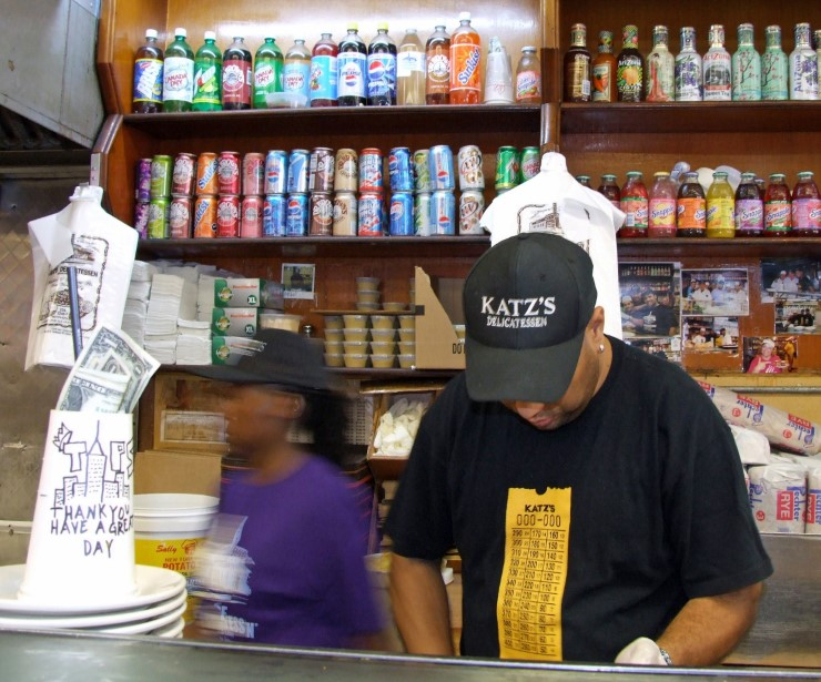 Man at counter in a deli with drinks cans on shelves behind