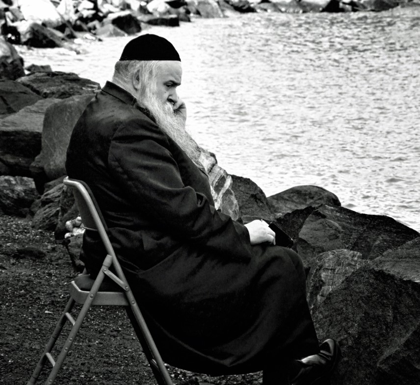 Man on a seat by water, black and white photo