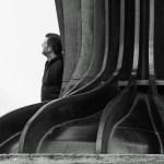 Feet of huge metal sculpture, with man standing beside
