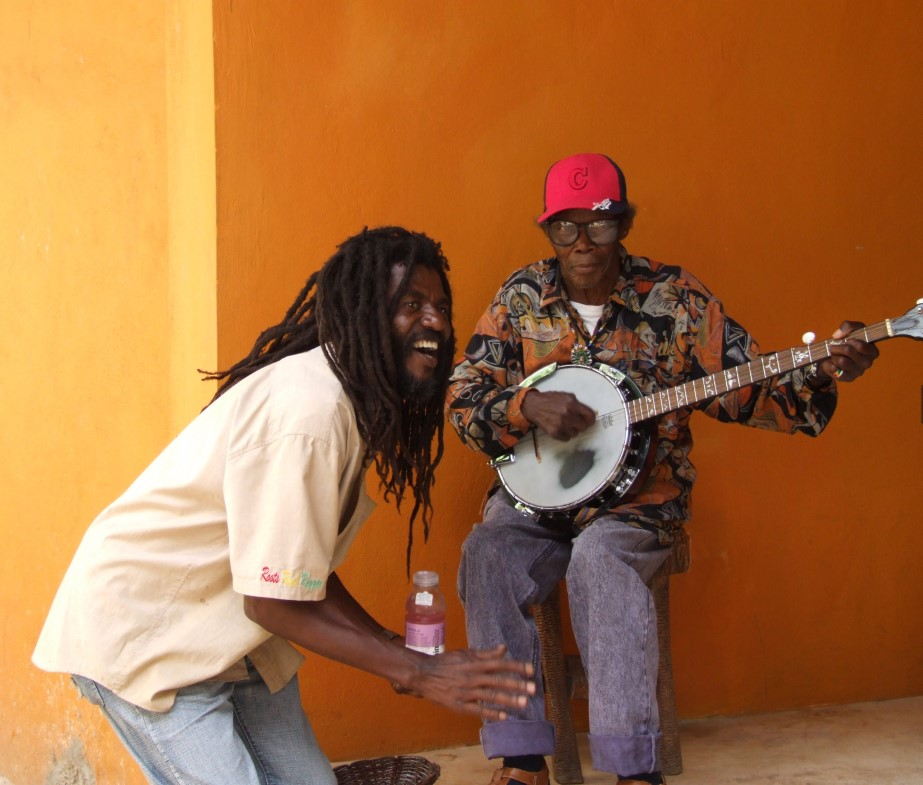 Man with dreadlocks and another playing banjo