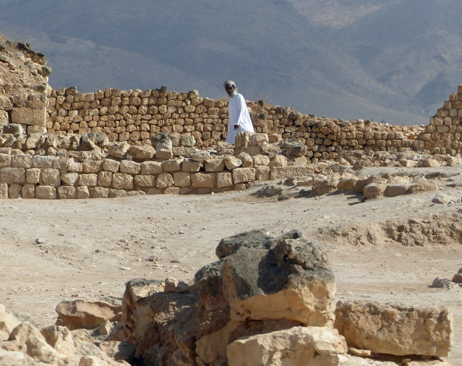Man in white robes walking past ruined walls