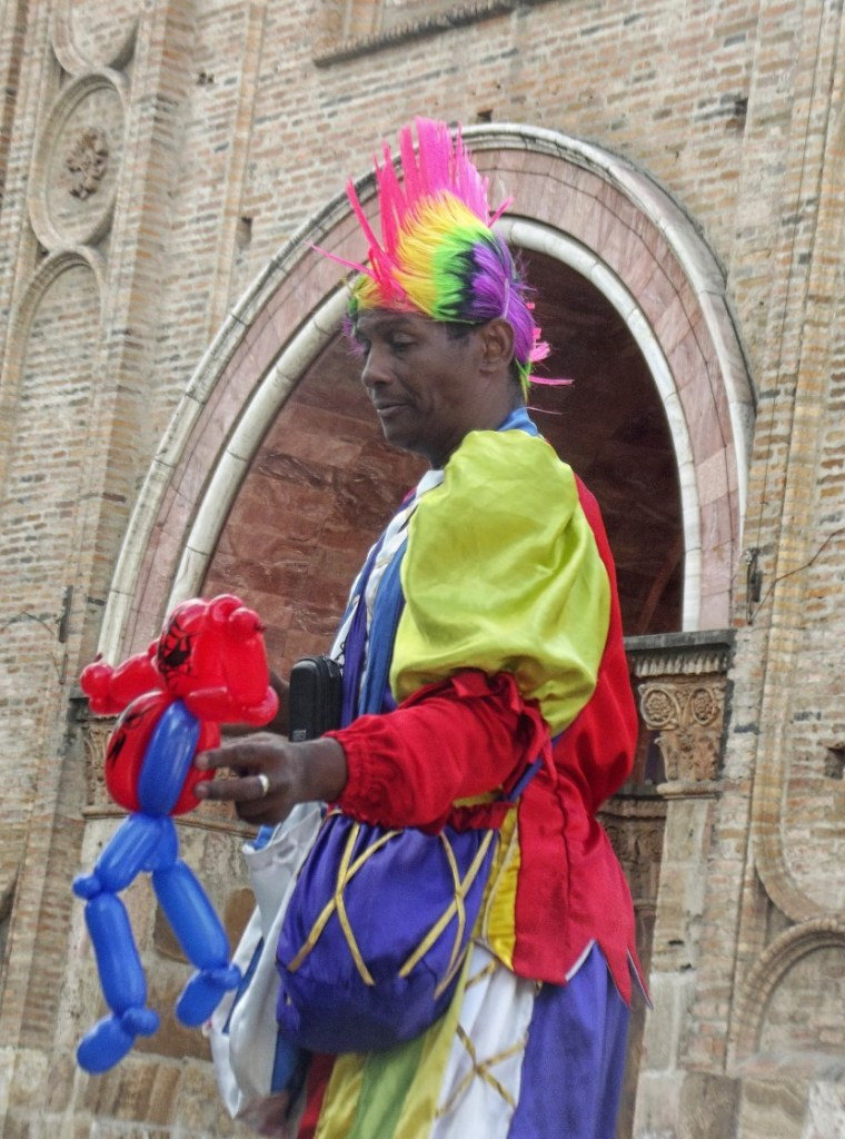 Colourfully dressed man on stilts