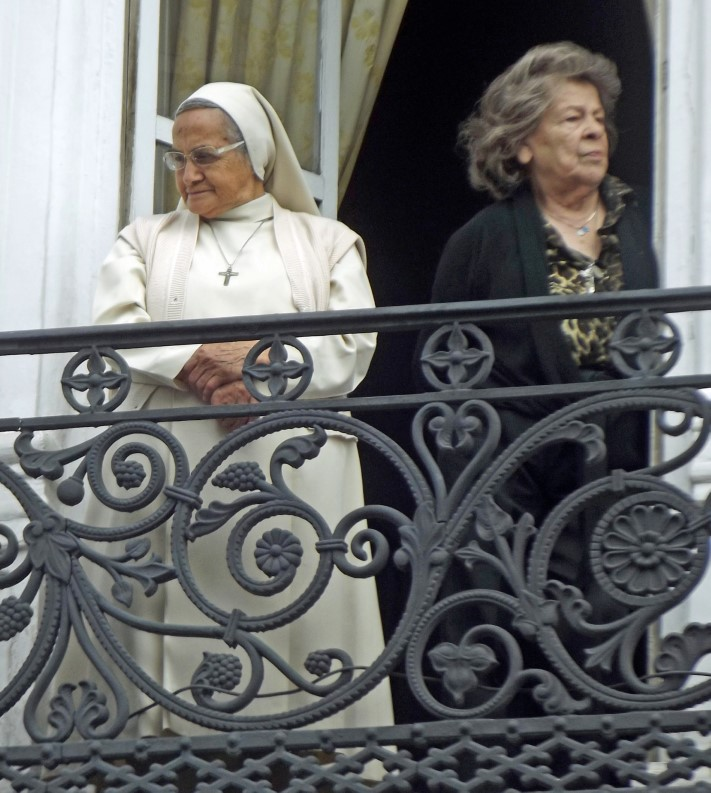 Nun in white and lady in black on a balcony