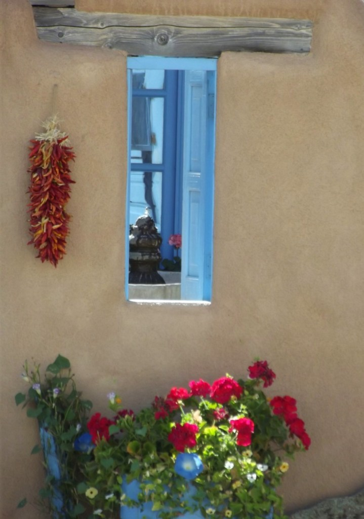 Adobe building with blue window frame and flowers