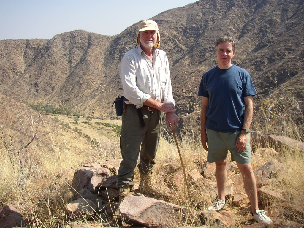 Two men on a hill in dry landscape