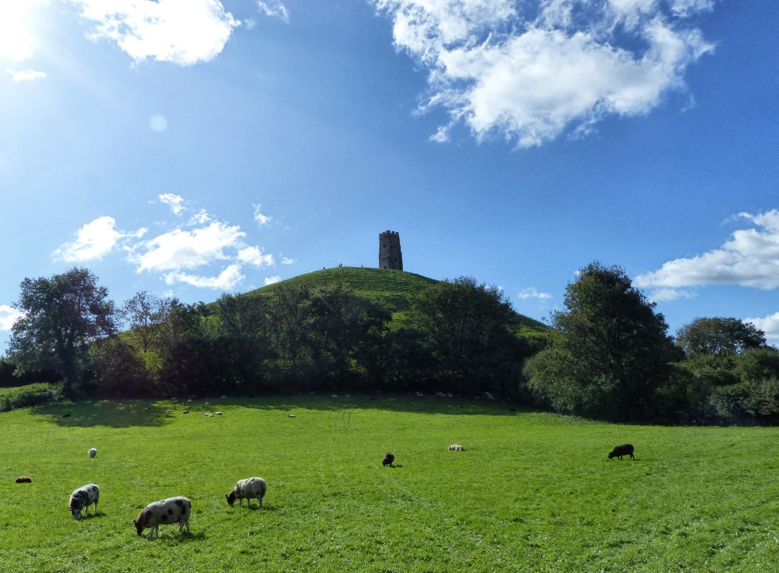 Church tower on a green hill with blue sky