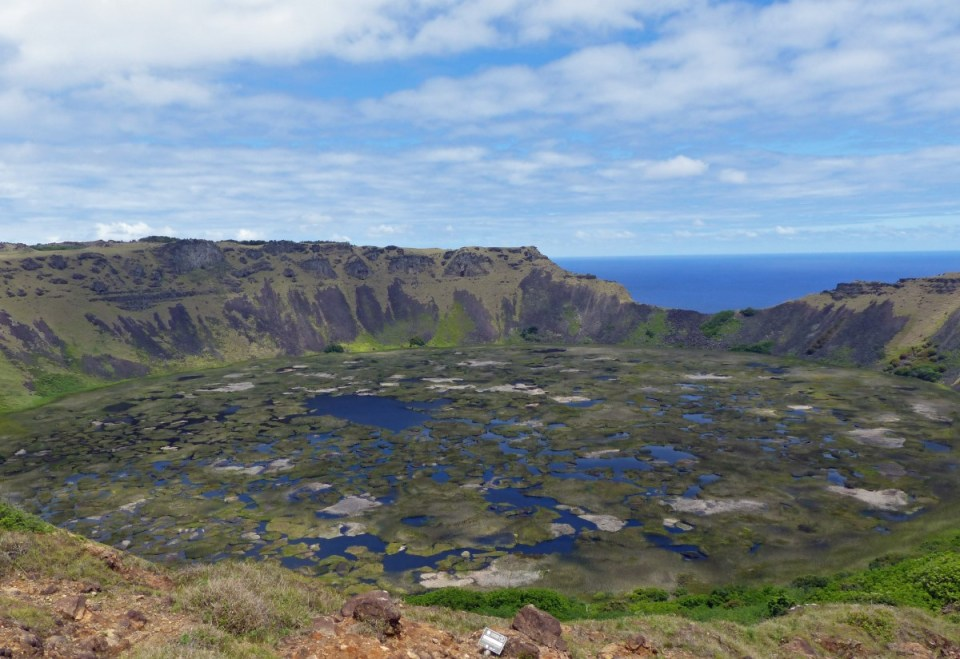 Volcanic crater with reeds on the water and sea beyond
