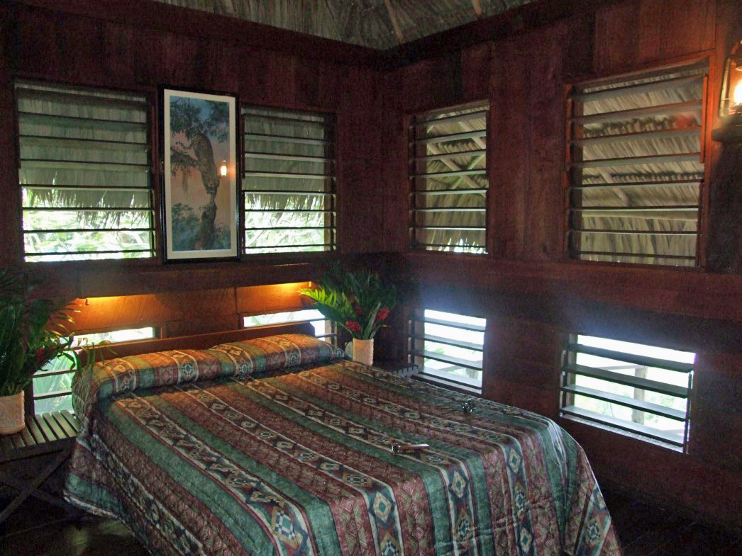 Bed in a wooden chalet with thatch roof