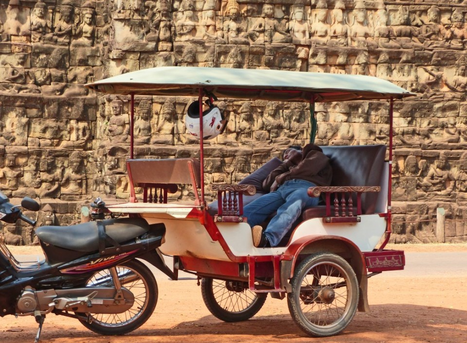 Man sleeping in a tuk tuk by a carved stone wall