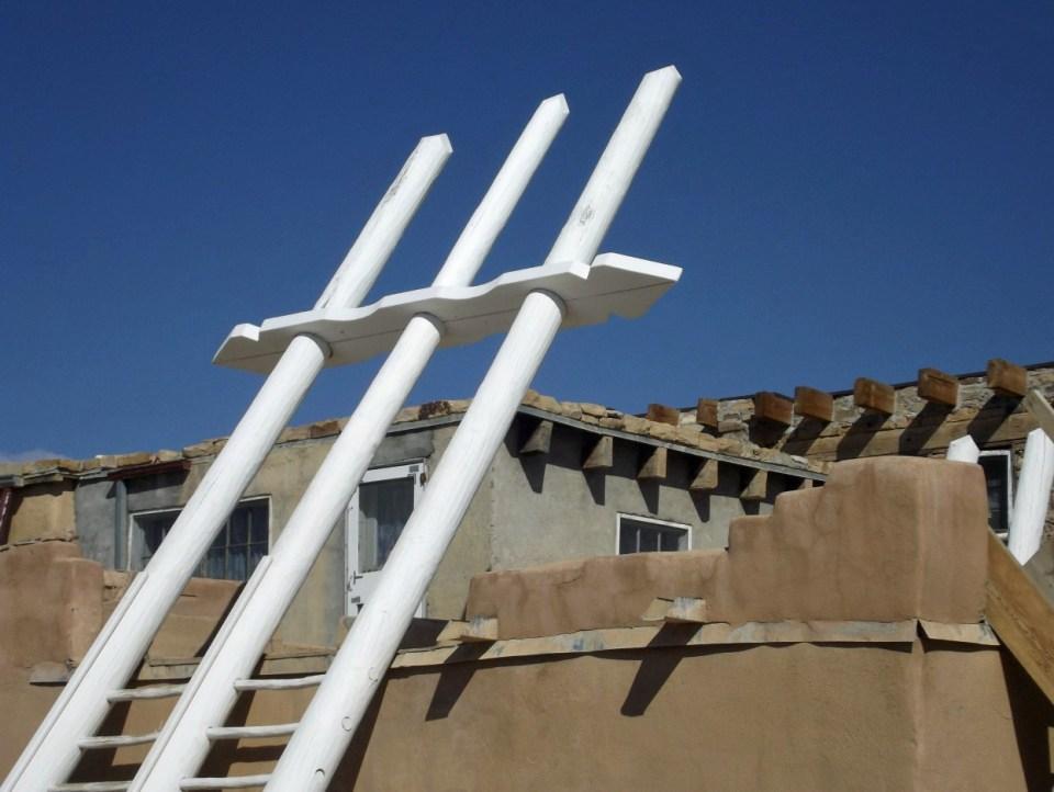 White ladder against an adobe house