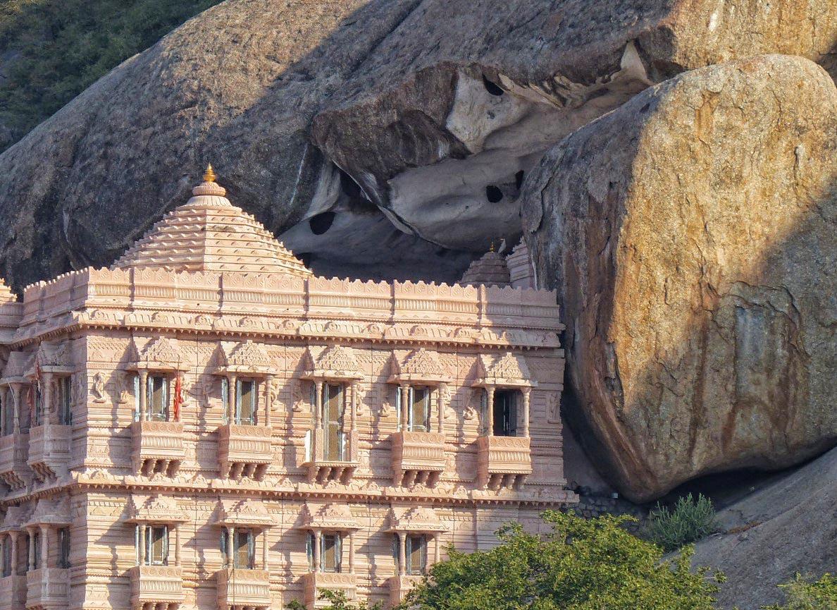 Stone building nestled against hillside with huge boulders