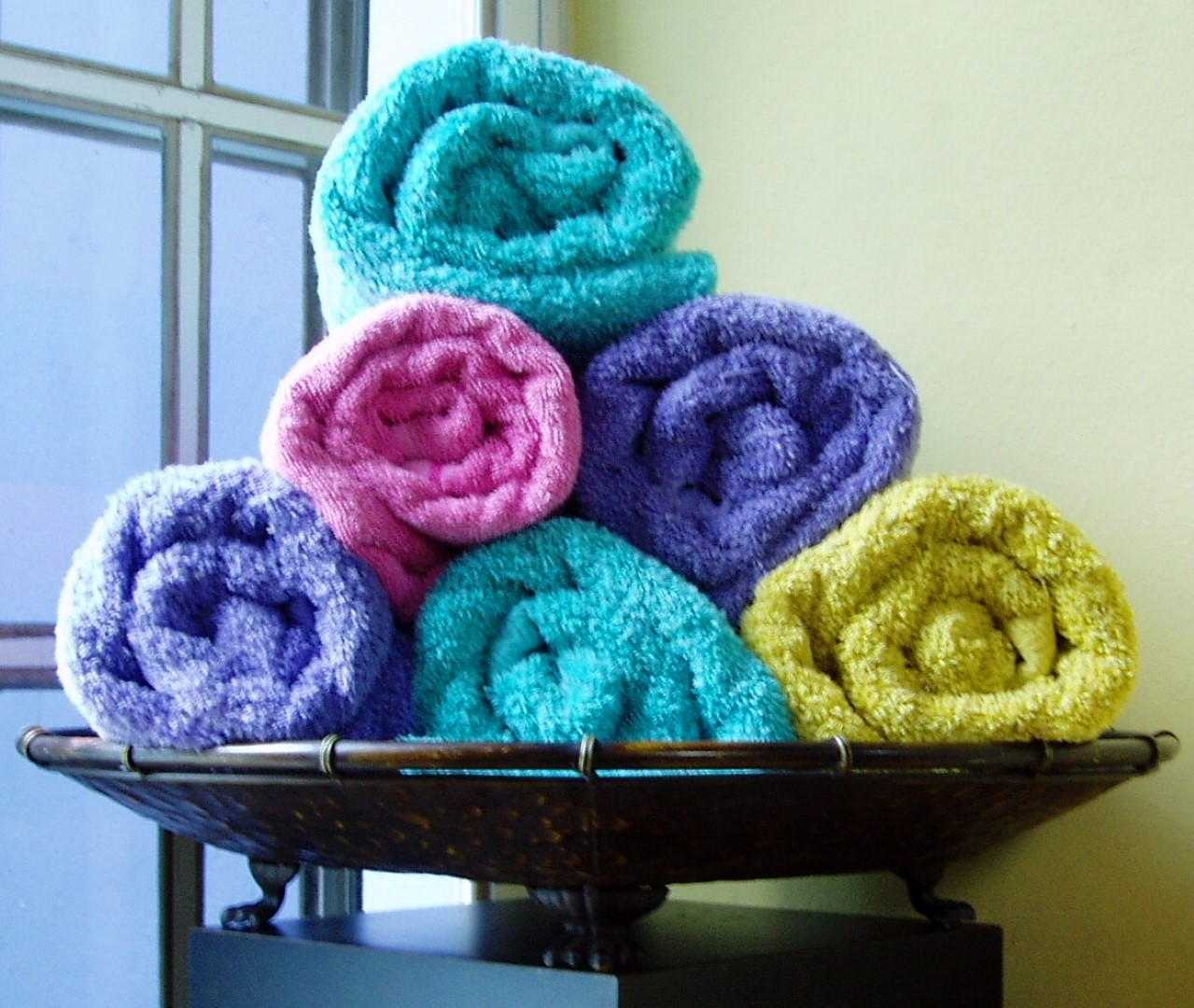 Different coloured towels rolled up