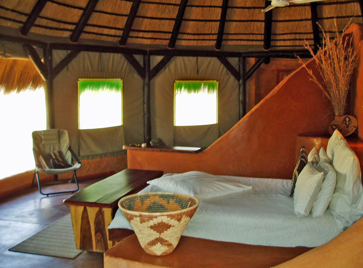 Bed in round adobe room with canvas walls